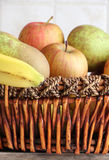 Fruit basket. Detail of a fruit basket with some pears and apples and bananas, inside a kitchen, portrait cut Royalty Free Stock Photos