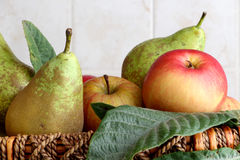 Fruit basket. Detail of a fruit basket with some pears and apples, inside a kitchen, landscape cut Stock Photo