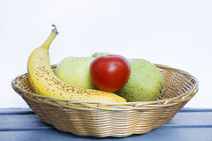 Fruit basket. Basket filled with a banana,apple,tomato and a pear Stock Photos