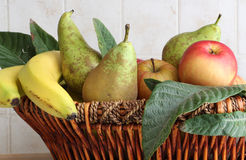 Fruit basket inside a kitchen. Detail of a fruit basket with some pears and apples and bananas, inside a kitchen, landscape cut Stock Photography