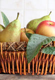 Fruit basket in a kitchen. Detail of a fruit basket with some pears and apples, inside a kitchen, portrait cut Stock Photos