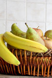 Fruit basket in a kitchen, space for text. Detail of a fruit basket with some pears and apples and bananas, inside a kitchen, space for text on top, portrait cut Stock Photo