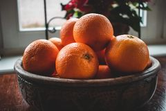 A fruit basket with large oranges on a wooden table royalty free stock images
