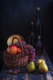 Fruit in a basket,  melon and bottles with wine in style  rustic Royalty Free Stock Images