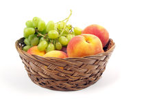 Fruit basket. Of peaches and grapes on a white background Stock Images
