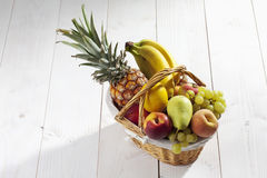 Fruit basket with pineapple, bananas, lemon, apple, peaches, grapes on white wooden background stock photos