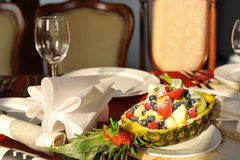 Fruit basket on the set table. Pineapple basket with fruits on the set table Royalty Free Stock Photos