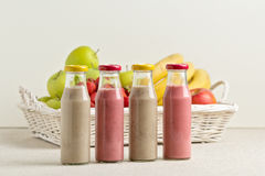 Fruit basket and strawberry and banana smoothie in a glass bottl Royalty Free Stock Image