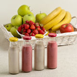 Fruit basket and strawberry and banana smoothie in a glass bottl Stock Image