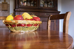 Fruit basket on the table. Fresh fruit basket on a wooden circular table in the kitchen with a pantry on the background Stock Image