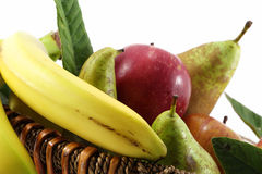 Fruit basket on white. Detail of a fruit basket with some pears and apples and bananas, landscape cut Royalty Free Stock Photography