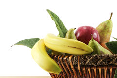 Fruit basket on white, space for text. Detail of a fruit basket with some pears and apples and bananas, inside a kitchen, landscape cut Stock Photos