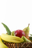 Fruit basket on white, space for text. Detail of a fruit basket with some pears and apples and bananas, space for text on top, portrait cut Stock Photo