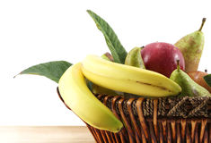 Fruit basket on white, space for text. Detail of a fruit basket with some pears and apples and bananas, on a wooden chopping board, space for text on the left Stock Photos