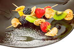 Fruit, Berries and mini blini kebab on black plate, dusted with Stock Photography