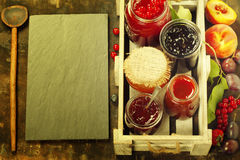 Fruit and berry jam on a rustic background Royalty Free Stock Photos