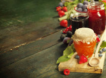 Fruit and berry jam on a wooden background Royalty Free Stock Image