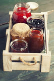 Fruit and berry jam on a wooden background Royalty Free Stock Photography