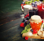 Fruit and berry jam on a wooden background Stock Photography