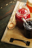 Fruit and berry jam on a wooden background Stock Photos