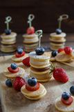 Fruit, berry and pancake canapes on wooden table. Fruit, berry and pancake very small canapes on wooden table. Sweet candybar for children stock photo