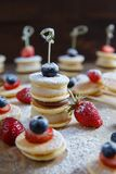 Fruit, berry and pancake canapes on wooden table. Fruit, berry and pancake very small canapes on wooden table. Sweet candybar for children`s holliday royalty free stock images
