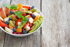 Fruit and berry salad in a bowl on a wooden background Royalty Free Stock Images