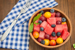 Fruit and berry salad of watermelon, blueberries, plums, currants, gooseberry, cherry plum. Wooden background. Top view. Fruit and berry salad of watermelon Royalty Free Stock Photo