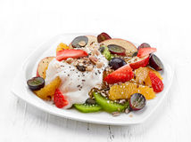 Fruit and berry salad on white plate Stock Images