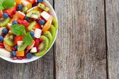Fruit and berry salad and wooden background, horizontal Royalty Free Stock Image