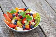 Fruit and berry salad on wooden table, horizontal Stock Images