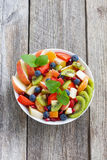 Fruit and berry salad on wooden table, vertical top view Royalty Free Stock Photos