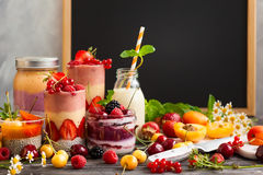 Fruit berry smoothie. Clean eating ideas for breakfast or snack. Assortment of  berry fruit  smoothies, juices and chia seeds pudding in front of a chalkboard Royalty Free Stock Photo