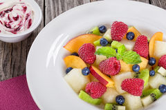 Fruit and berry summer dessert salad decorated with mint Stock Photography