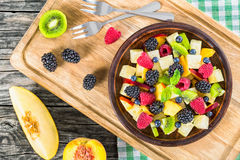 Fruit and berry summer salad decorated with mint leaves Stock Photos