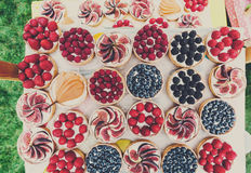 Fruit and Berry tarts dessert assorted top view background. Fruit and berry tartlets dessert tray assorted top view background. Beautiful delicious tarts, pastry Stock Photo