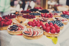 Fruit and berry tarts dessert tray assorted outdoors Royalty Free Stock Image