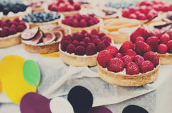 Fruit and berry tarts dessert tray assorted outdoors Stock Photos