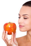 Fruit is the best snack. Cropped shot of attractive young woman holding an apple in hand with closed eyes against white isolated background Stock Image