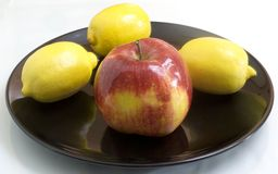 Fruit on a black plate. The red-yellow apple and lemons lie on a black plate and are reflected Stock Photos