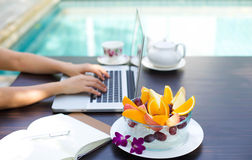 Fruit blow and Business people working at home. Business people working at home on laptop computer with blows of fresh fruit by swimming pool stock image