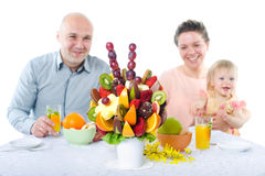 Fruit bouquet decoration on the dining table. In front of happy family, fruit bouquet in focus Royalty Free Stock Image
