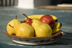 Fruit bowl 1. An assortment of pears and bananas in a brown ceramic dish Stock Image