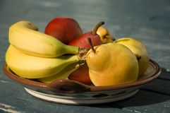 Fruit bowl. An assortment of pears and bananas in a brown ceramic dish Royalty Free Stock Photo