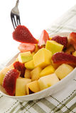 Fruit bowl. A shot of a fork picking a strawberry from a fruit bowl Royalty Free Stock Photography