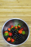 Fruit bowl on bamboo mat Royalty Free Stock Images