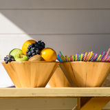 Fruit Bowl And Colorful Straws On Table Stock Photos
