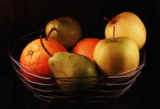 Fruit bowl. A bowl of fresh fruit on a black background royalty free stock photos
