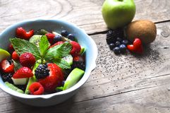 Fruit Bowl with Mint. Apple, kiwi, heart shaped strawberries, chia seeds, blue berries, black berries, apples, raspberry, wooden background, natural fruit bowl Stock Photos