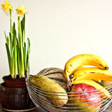 Fruit bowl and narcissus flowers Stock Images